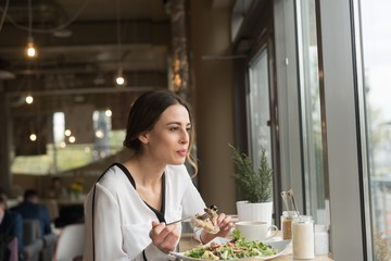 Woman looking away eating food