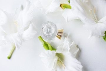 Small bottle of perfume with flowers over white