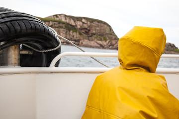 persona de espalda con un impermeable amarillo en un barco bajo la lluvia