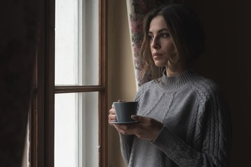Close up of thoughtful woman having coffee while standing by