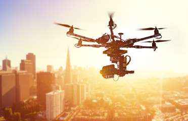 Drone Flying over San-Francisco city. Hexacopter drone with high resolution digital camera on the sky. Heavy lift drone photographing city at sunset. Toned photo with blurred background.