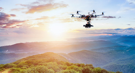 The drone with the professional camera takes pictures of the misty mountains at sunset