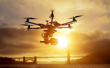 The drone with the professional cinema camera flying over the misty mountains at sunset. Blurred background. Innovation photography concept. Heavy lift drone photographing city at sunset.