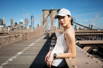 Pretty asian runner girl training outdoors working out at Brooklyn bridge with Manhattan, New York City in the background.