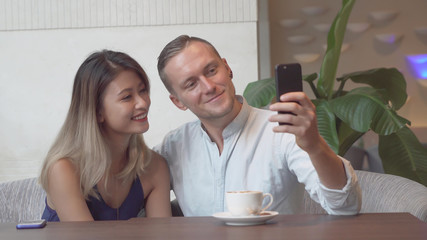 Multicultural couple taking self portrait using smartphone.
