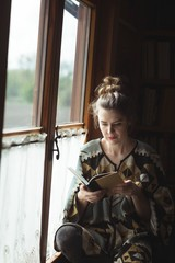 Woman sitting near window reading book