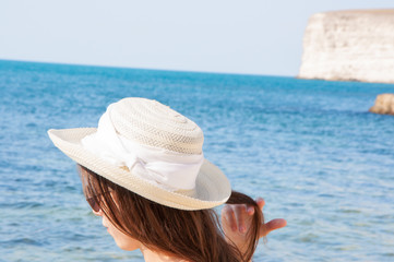 Beautiful girl in sunglasses and hat against the sea