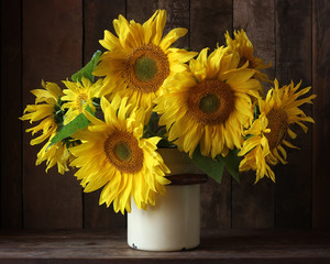 Bouquet of sunflowers in a can on a dark background.