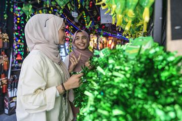 Two muslim ladies shopping for hari raya decorations.