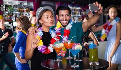 Couple making selfie with cocktails