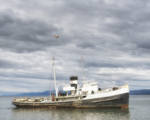 Wrecked abandoned ship near Ushuaia. Red airplane over it. Tierra del Fuego province in Argentina. Patagonia.