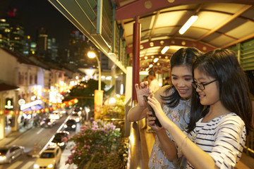 Mother and daughter taking a photo of light ups during Chinese New Year