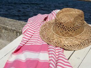 Badeurlaub: Sonnenhut und Strandtuch