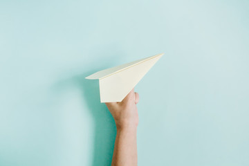 Women hand holding paper plane on pale blue background. Flat lay, top view.