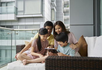 Smiling Family of four bonding on the balcony over an electronic tablet