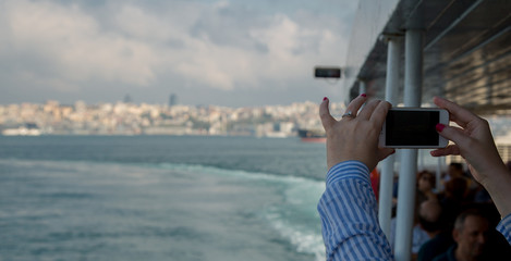 Woman looking at horizontal smartphone  takes pictures. Close up shot of woman's hands with mobile. Istambul, Turkey.