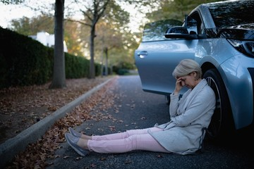 Worried woman sitting beside the car