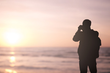 Silhouette traveler man holding camera for take a photo at beach ocean at sunset time background