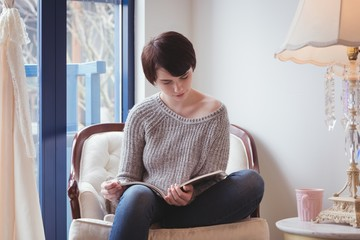 Woman reading a magazine at home
