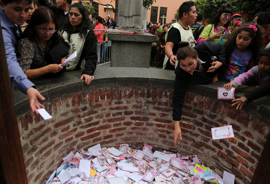 People throw letters into the well of wishes at Saint Rose's Church during celebrations for the anniversary of Santa Rosa de Lima in Lima