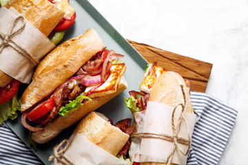 Photo sur Aluminium Snack Fresh baguette sandwich bahn-mi styled. Bacon, roasted cheese, tomatoes and lettuce on metallic tray on white marble background. Close up view.