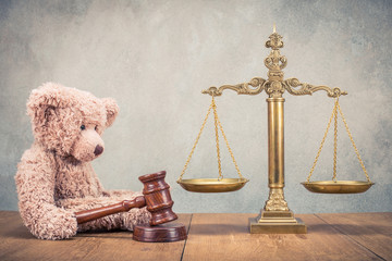 Bronze law scales and Teddy Bear with wooden gavel on table. Symbols of justice. Vintage old style filtered photo