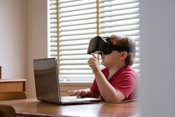 Boy wearing vr glasses while using laptop