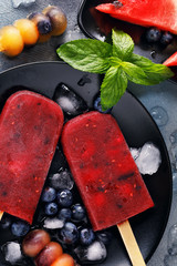 Fruit ice from watermelon, orange and blueberries with mint leaves. Top view of summer dessert