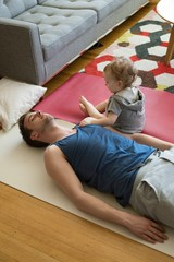 High angle view of girl sitting by father exercising on exercise