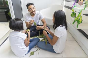 Father teaching his kids how to make ketupat