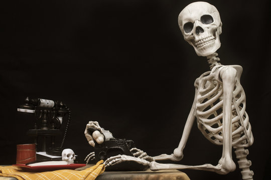 Halloween Skeleton At a Table with Typewriter, Phone and Cookies