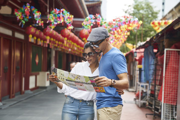 Happy tourists checking a map for directions outside Buddha Tooth Relic Temple