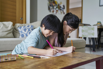 Siblings drawing at home