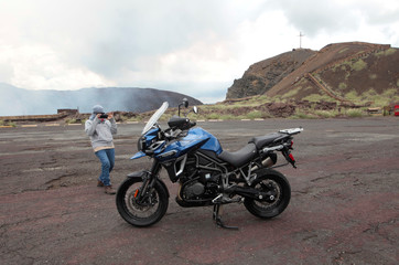 A man takes a pictures of a 1,200 cc motorcycle Triumph Explorer in Masaya