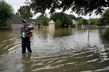 Nolan Witty carries his guitar he retrieved from his house in the Tropical Storm Harvey floodwaters in north western Houston