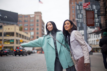 Two girlfriends flagging down a cab in Meatpacking district in New York