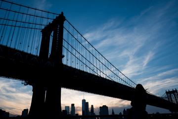 Silhouette of a Woman stands and looks at the Manhattan Bridge at sunset. Looking at the Manhattan Bridge and the New York City skyline at sunset, dramatic blue sky with wispy clouds.