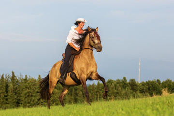 mature woman riding an Andalusian horse