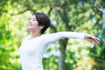 Young happy Asian woman exercising at the park.