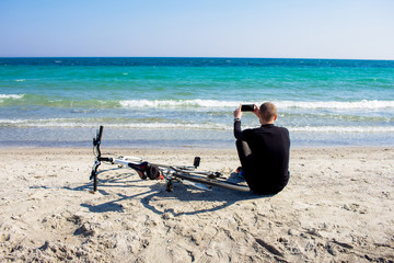 young man in black wear with white bicycle sitting and relaxing on the beach and use cellphone