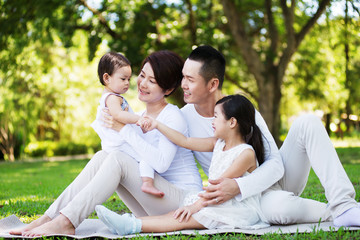Young happy Asian family spending time together at the park.