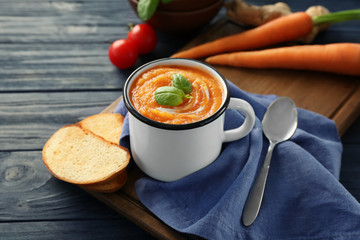 Cup with delicious carrot soup on table
