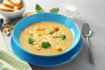 Plate with broccoli cheddar soup on table