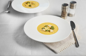 Plate with broccoli cheddar soup on kitchen table