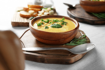 Bowl with broccoli cheddar soup on wooden board