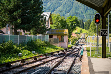 Little mountain train station empty rails in sunny summer day.