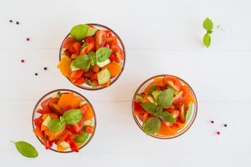 Healthy diet salad with fresh basil, red and yellow tomatoes, bell pepper in the small glass bowls, top view.