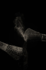 Make up brush with purple dust on black background