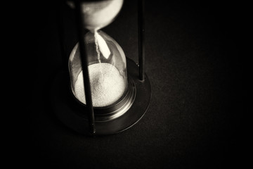 Large black hourglass against a black background
