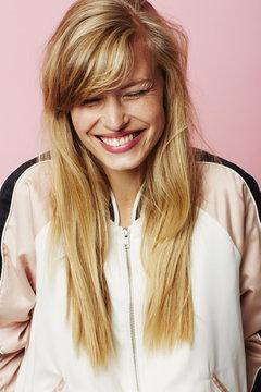 Beautiful blond woman in varsity jacket, laughing